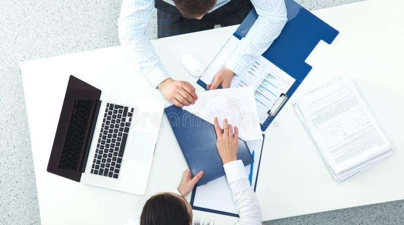 Бизнесмены сидя и обсуждая на деловой встрече, в офисе стоковая фотография
