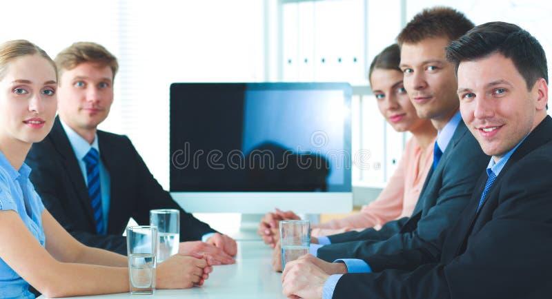 Бизнесмены сидя и обсуждая на деловой встрече, в офисе стоковое фото
