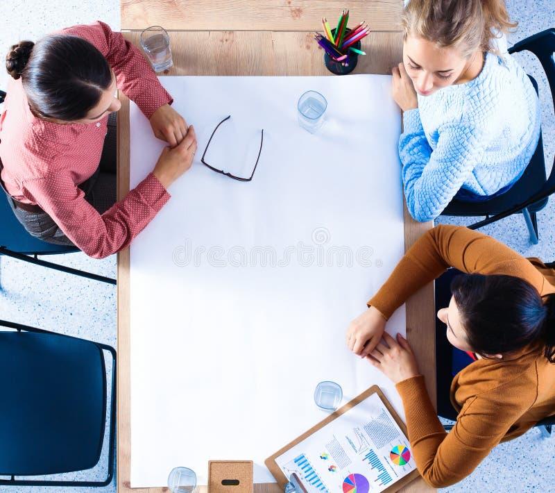 Бизнесмены сидя и обсуждая на встрече, в офисе стоковые изображения rf