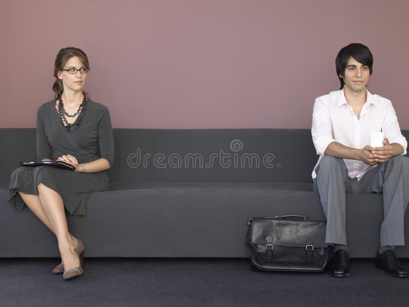 Бизнесмены сидя на софе в зале ожидания стоковая фотография