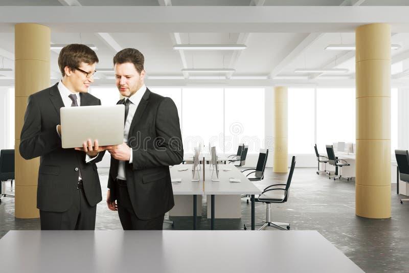 Бизнесмены смотря компьтер-книжку в современном офисе стиля просторной квартиры стоковая фотография