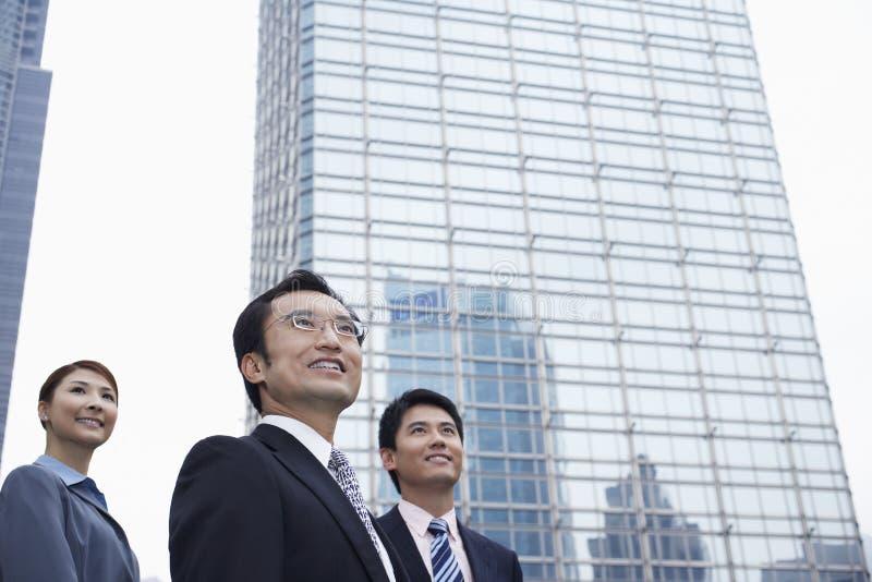 Бизнесмены смотря прочь перед зданием стоковое изображение rf