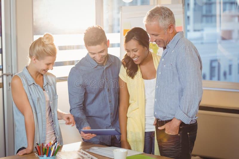 Бизнесмены смотря цифровую таблетку в конференц-зале стоковые изображения