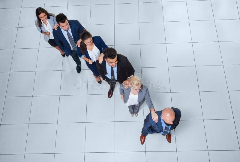 Бизнесмены собирают стоящий круг держа руки на современном взгляд сверху офиса стоковые фотографии rf