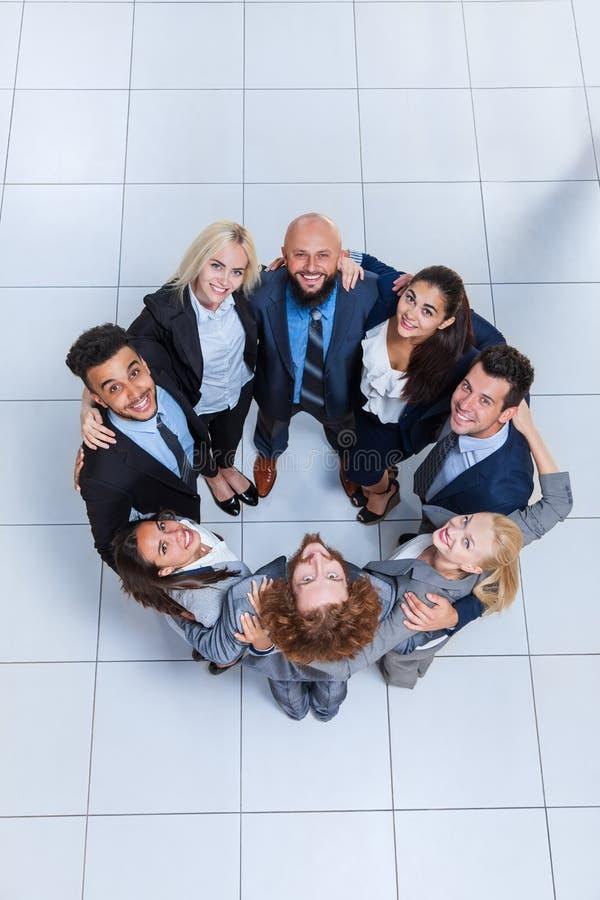 Бизнесмены собирают счастливую улыбку стоя на современном взгляд сверху офиса стоковое фото