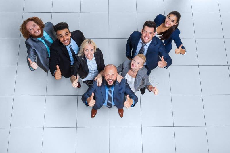 Бизнесмены собирают счастливую улыбку стоя на современном взгляд сверху офиса стоковое изображение