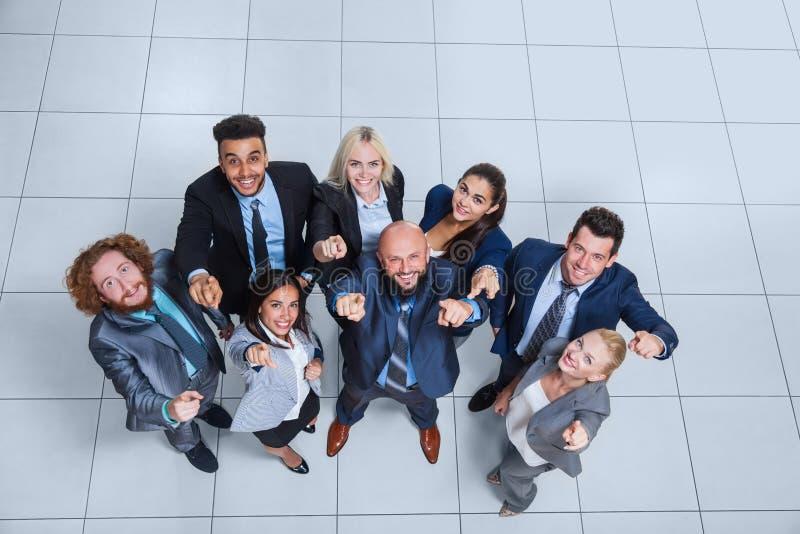 Бизнесмены собирают счастливую улыбку стоя на современном взгляд сверху офиса стоковая фотография rf