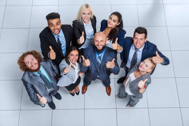 Бизнесмены собирают счастливую улыбку стоя на современном взгляд сверху офиса стоковое изображение rf
