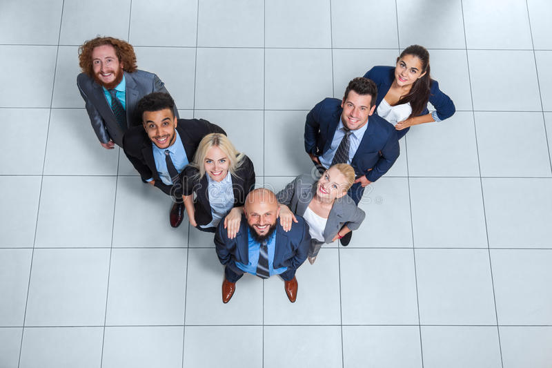 Бизнесмены собирают счастливую улыбку стоя на современном взгляд сверху офиса стоковые фотографии rf