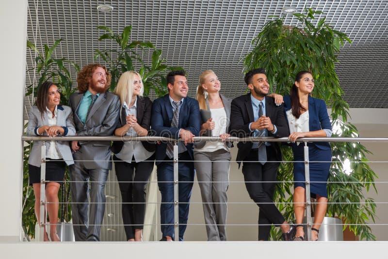 Бизнесмены собирают счастливую улыбку стоя на современном офисе смотря, что вверх скопировали космос стоковое изображение rf