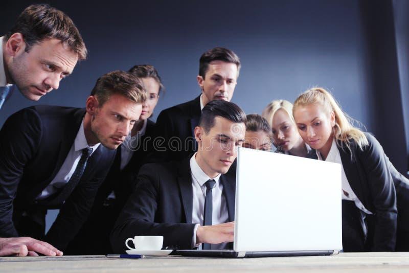 Бизнесмены собранные вокруг компьтер-книжки стоковые фотографии rf