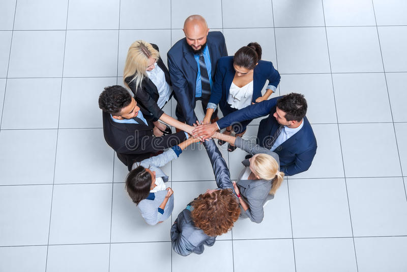 Бизнесмены стойки группы в круге, команде предпринимателей кладя их сотрудничество сыгранности стога рук стоковые фото