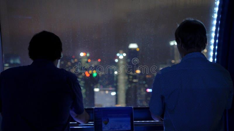 Бизнесмены стоят на колесе ferris на взглядах ночи на зданиях в предпосылке города Сингапура стоковое фото