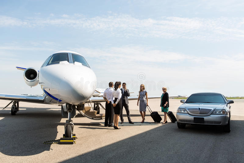 Бизнесмены с пилотом и стюардессой на стоковая фотография