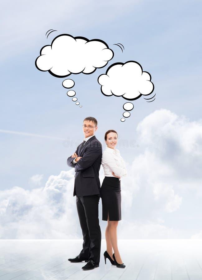 Бизнесмены с думая облаками на предпосылке неба стоковые фото