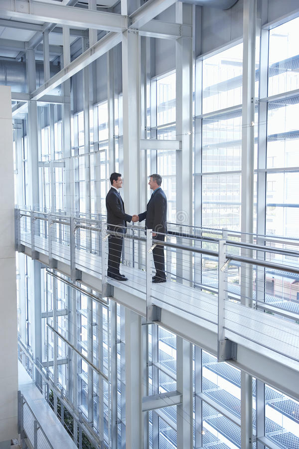 Бизнесмены тряся руки в современном офисе стоковое фото rf