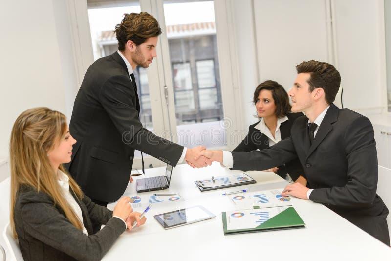 Бизнесмены тряся руки, заканчивая вверх встречу стоковое фото