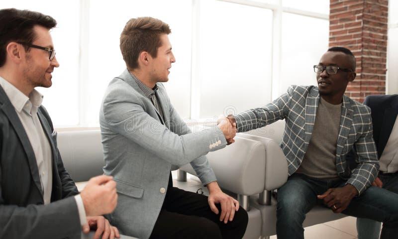 Бизнесмены тряся руки сидя в лобби делового центра стоковое изображение rf