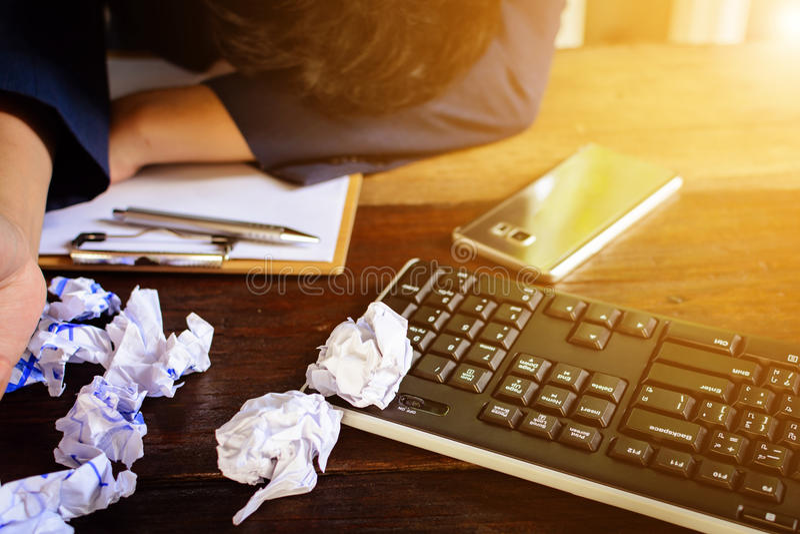 Бизнесмены усиливают и опасаются задавленную бумагу на деревянной таблице стоковые изображения