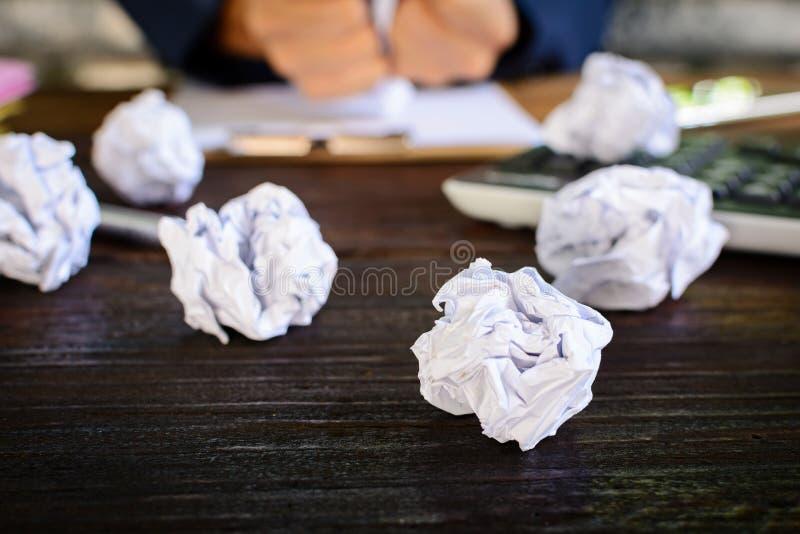 Бизнесмены усиливают и опасаются задавленную бумагу на деревянной таблице стоковое фото