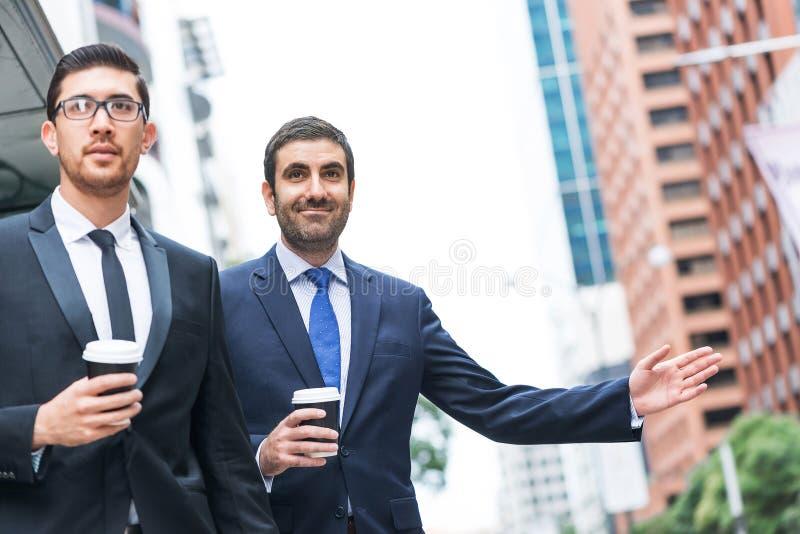 Бизнесмены улавливая такси стоковые фото