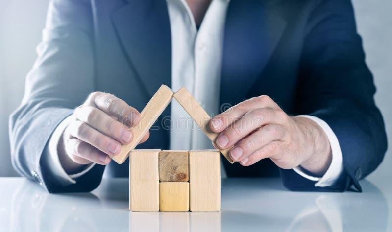 Бизнесмен, агент недвижимости, страховой инспектор или архитектор аранжируя и держа защищая крышу над домом сделанным из деревянн стоковое фото rf