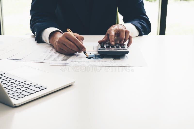 Бизнесмен анализируя диаграмму отчет о с калькулятором в офисе стоковые фото