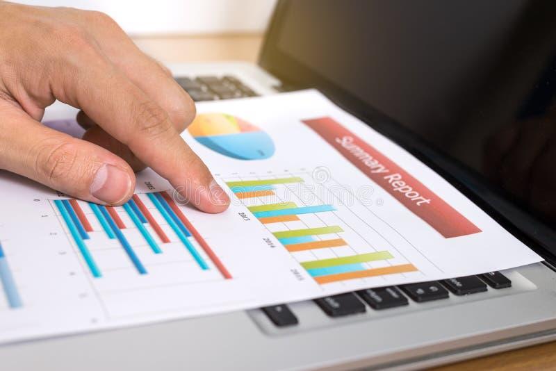 Бизнесмен анализируя диаграммы вклада с компьтер-книжкой Финансы mar стоковое фото