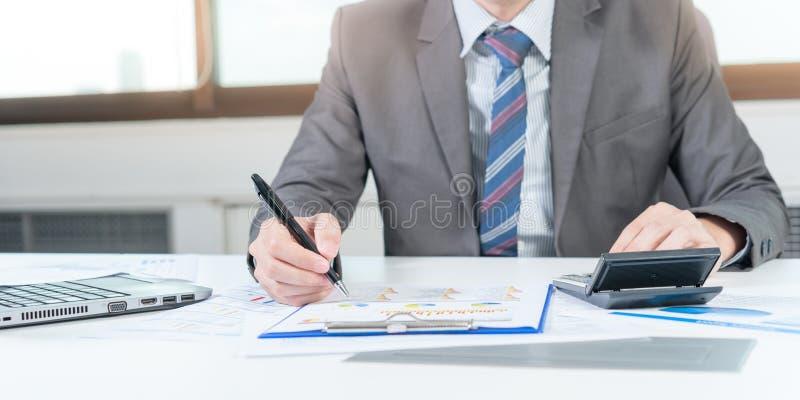 Бизнесмен анализируя диаграмму отчет о с компьтер-книжкой и калькулятором стоковое фото rf