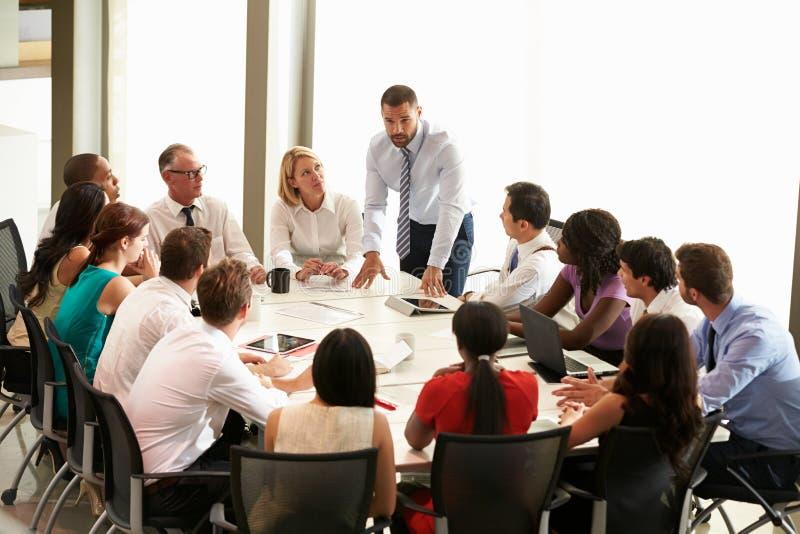 Бизнесмен адресуя встречу вокруг таблицы зала заседаний правления стоковые фотографии rf