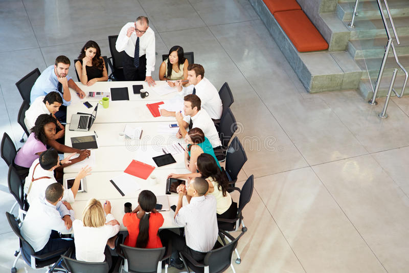 Бизнесмен адресуя встречу вокруг таблицы зала заседаний правления стоковые изображения