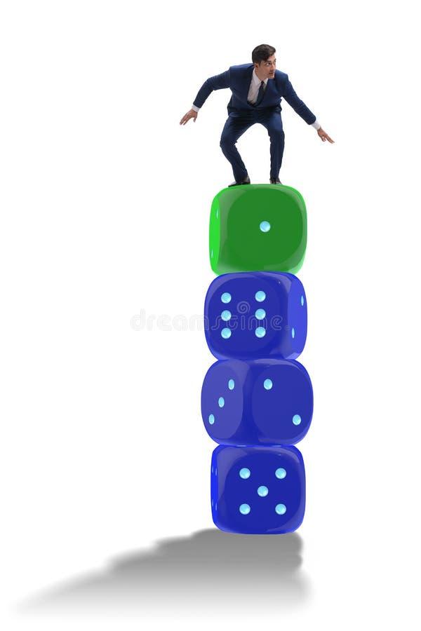 Бизнесмен балансируя na górze стога кости в concep неопределенности стоковое изображение