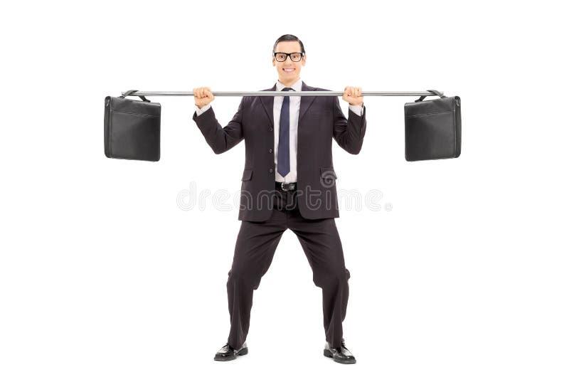 Бизнесмен балансируя 2 портфеля на трубе стоковая фотография