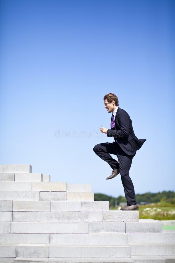 Бизнесмен бежать вверх лестницы стоковое фото