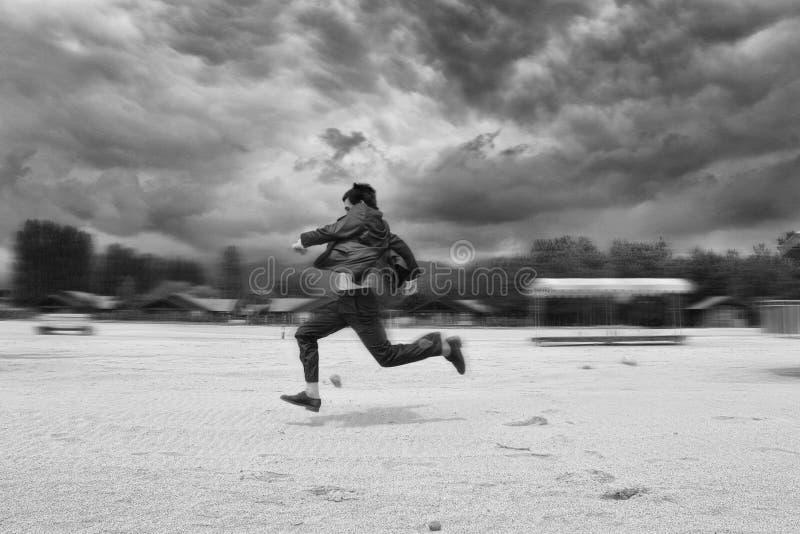 Бизнесмен бежать в пляже нерезкость предпосылки запачкала движение frisbee задвижки скача к стоковые фото