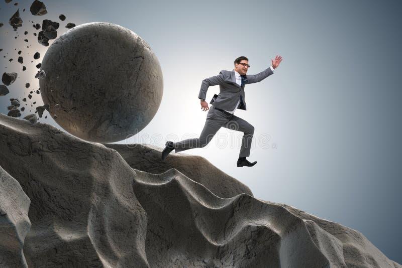 Бизнесмен бежать далеко от падая Rolling Stone стоковые фото