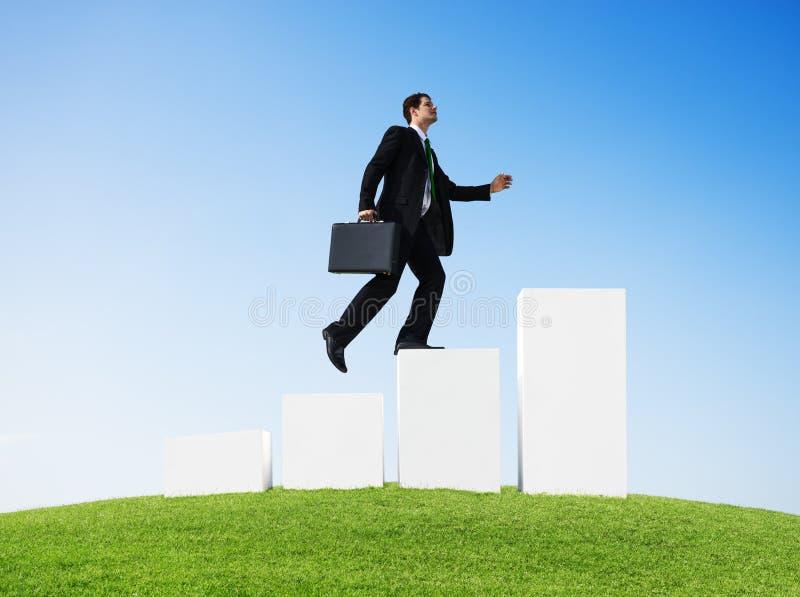 Бизнесмен бежать к верхней части столбчатой диаграммы стоковое фото rf