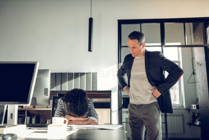 Бизнесмен браня его секретаршу для не завершать задачи стоковое фото
