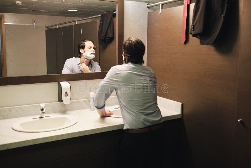 Бизнесмен брея в Bathroom офиса после раннего утра коммутирует стоковые фотографии rf