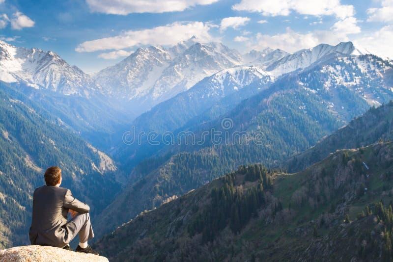 Бизнесмен вверху усаживание и думать горы стоковая фотография rf