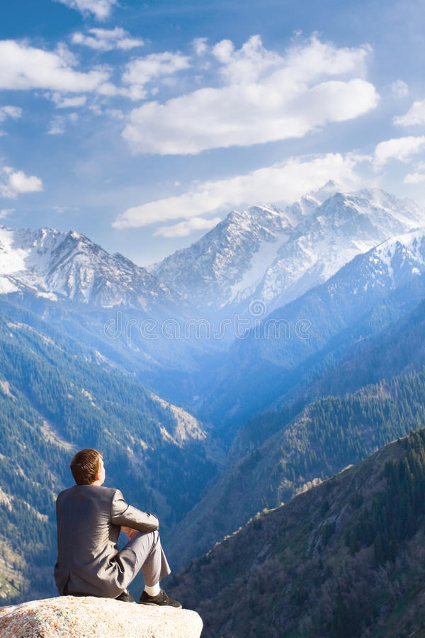 Бизнесмен вверху усаживание и думать горы стоковое изображение rf