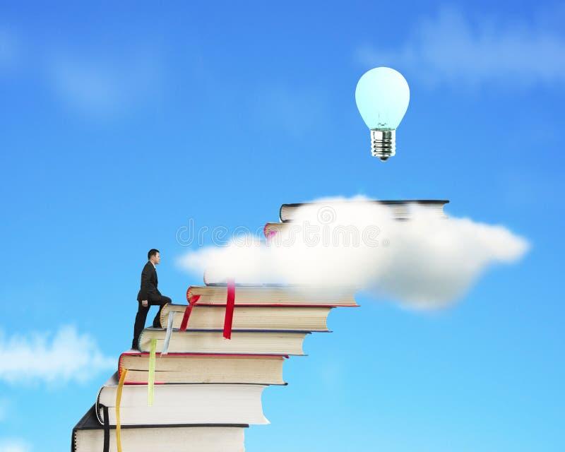 Бизнесмен взбираясь на стоге книг для достижения шарика стоковое изображение rf