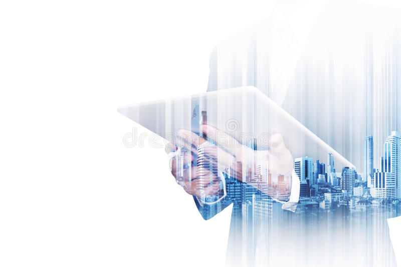Бизнесмен двойной экспозиции работая на цифровой таблетке с современными зданиями в городе, изолированном на белой предпосылке стоковое фото