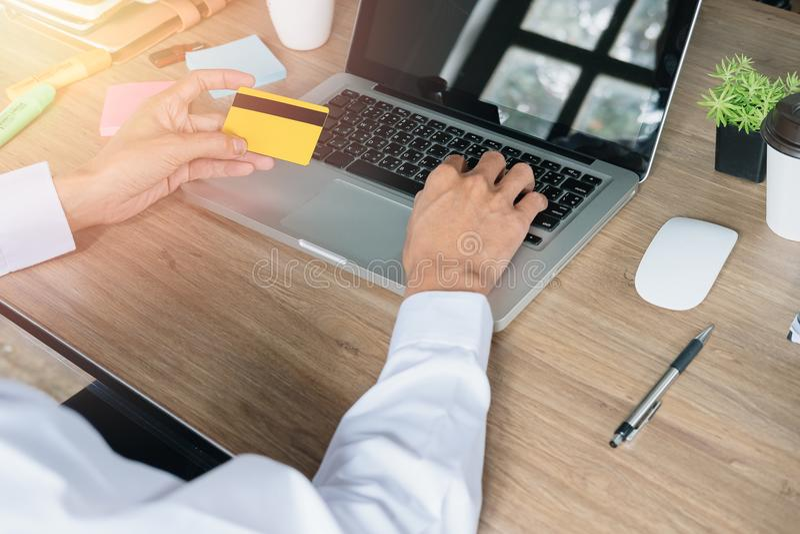 Бизнесмен вручает держать кредитную карточку и использование компьтер-книжки стоковая фотография