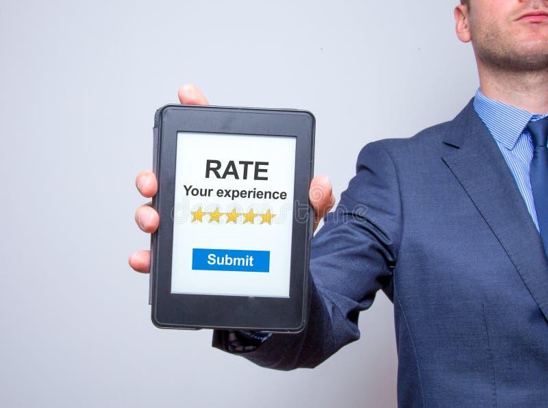 Бизнесмен вручает держать таблетку с тарифом ваш опыт Busi стоковые фото