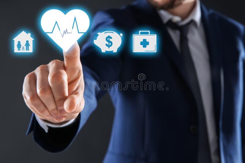Бизнесмен выбирая значок сердца на виртуальном экране против темной предпосылки стоковая фотография rf