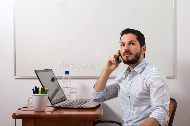 Бизнесмен вызывая и смотря далеко стоковые фото