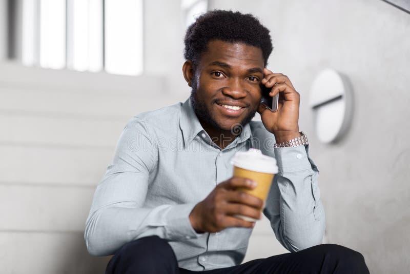 Бизнесмен вызывая на smartphone на лестницах офиса стоковая фотография rf
