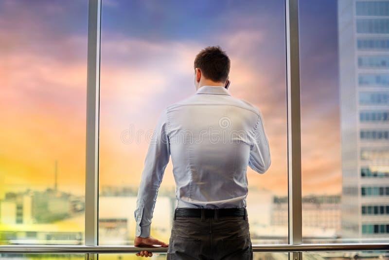 Бизнесмен вызывая на smartphone на окне офиса стоковое изображение