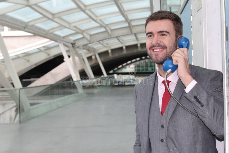 Бизнесмен вызывая общественным телефоном на авиапорте стоковое фото rf